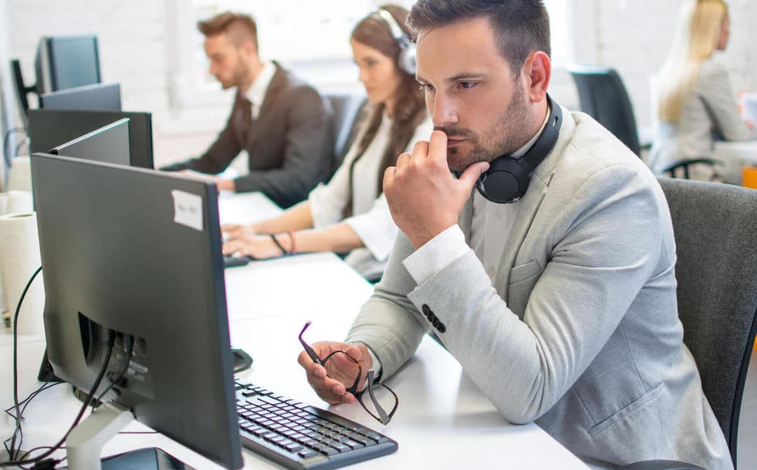 Pensive male it-support worker with eyeglasses in hand thinking about how to solve the problem