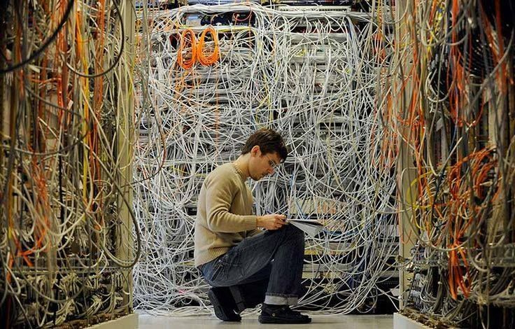 A man with a pad and pencil surrounded by tons of crossed wires